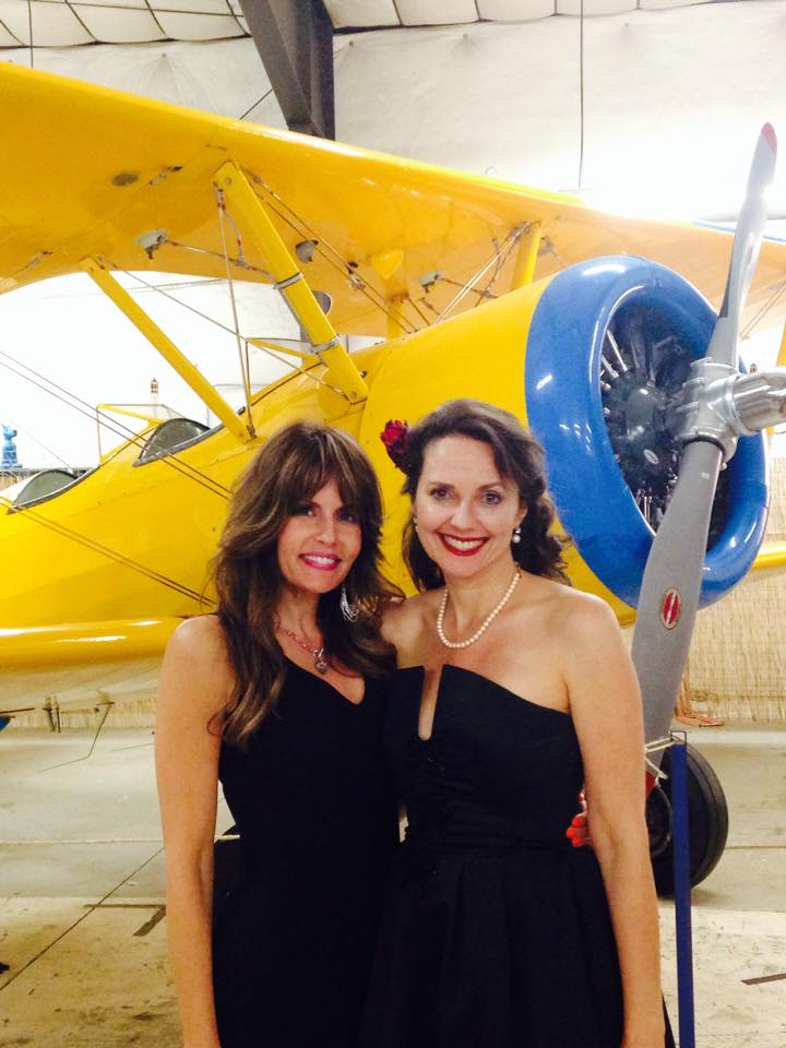 Photo of Elizabeth Montgomery with a friend near a yellow airplane